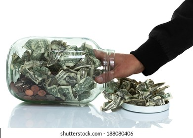 Glass jar full of money tipped over on its side spilling money with hand reaching in