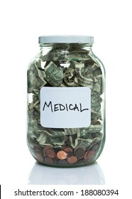 Glass jar full of money with a white medical label