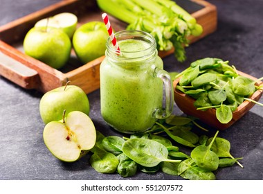 glass  jar of green juice smoothie with spinach, apple and celery on dark background.
