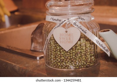 Glass jar with green peas inside and white hand-made labeled ribbon and wooden heart entitled home sweet home on blurred kitchen sink background