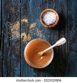 Glass jar of homemade salted caramel sauce with spoon, brown sugar and bowl of salt. Over old dark blue wooden background. Top view with space. Square image