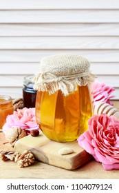 Glass jar of honey among pink roses.