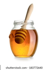 Glass jar of honey with dipper isolated on white background