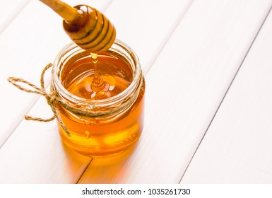 Glass jar with honey and dipper on white wooden table background.