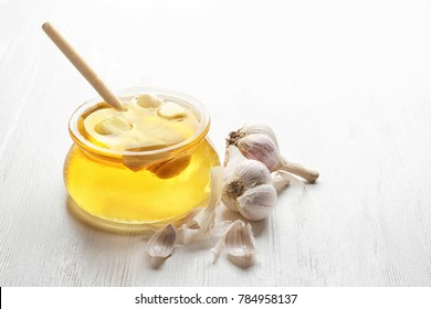 Glass jar with honey and garlic on white wooden background