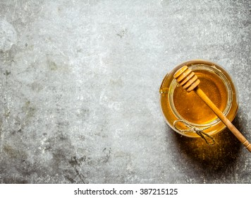 Glass jar with honey . On a stone background.
