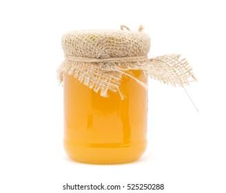 glass jar of honey on white background