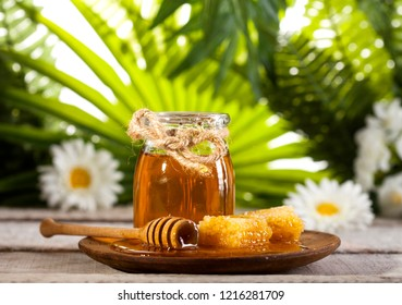 Glass jar of honey with wooden drizzler and chomomile on a white wooden table and green leaves background.