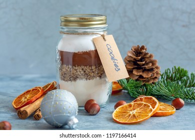 Glass jar with ingredients for baking chocolate nut cookies. Idea for Christmas gift.