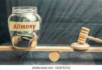 "Glass jar and the inscription ""Alimony"" and the hammer of the judge are on the scales. Payment of alimony of one of the spouses. Debt. Child custody. Judgment. Justice. Divorce. Court"