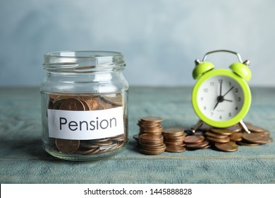 Glass jar with label PENSION and coins near alarm clock on wooden table