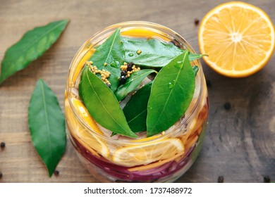 Glass jar with layered food, pickled onions, lemon, fish, bay leaf pepper and mustard on a blurred wooden background with juicy lemon. An example of a delicious home cooked dish
