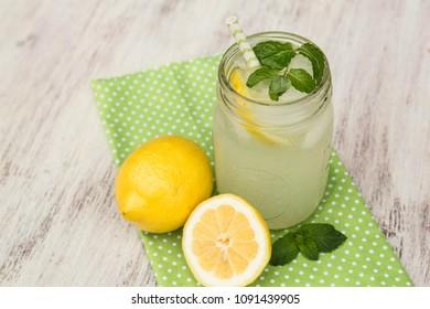 Glass jar of lemonade with lemons on green napkin and white wood background outside