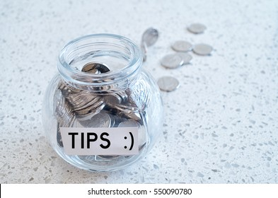 Glass jar with many coins and tips word  over a marble counter top