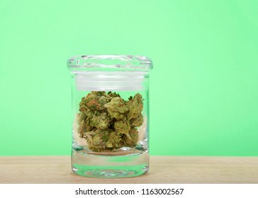 Glass jar with marijuana buds laying on a light wood table with bright mint green background