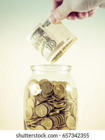 Glass jar with money on a white background. Hand with money