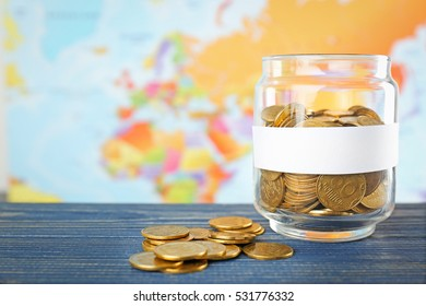 Glass jar with money on world map background