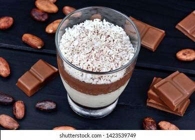Glass jar with mousse of chocolate and coconut flakes on black wooden background