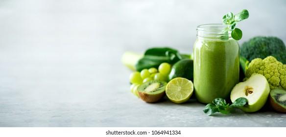 Glass jar mugs with green health smoothie, kale leaves, lime, apple, kiwi, grapes, banana, avocado, lettuce. Copy space. Raw, vegan, vegetarian, alkaline food concept. Banner. - Shutterstock ID 1064941334