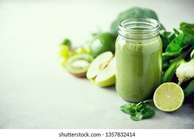 Glass jar mugs with green health smoothie, kale leaves, lime, apple, kiwi, grapes, banana, avocado, lettuce. Copy space, sunlight effect. Raw, vegan, vegetarian, detox, alkaline food concept - Shutterstock ID 1357832414