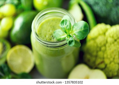 Glass jar mugs with green health smoothie, kale leaves, lime, apple, kiwi, grapes, banana, avocado, lettuce. Copy space. Raw, vegan, vegetarian, alkaline food concept. Banner.