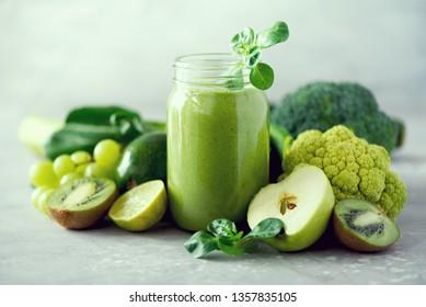 Glass jar mugs with green health smoothie, kale leaves, lime, apple, kiwi, grapes, banana, avocado, lettuce. Copy space. Raw, vegan, vegetarian, alkaline food concept. Banner.