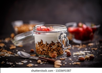 Glass jar of oat granola with yogurt and fresh strawberries for healthy breakfast