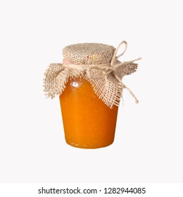 a glass jar of orange jam, the lid on top is tied with a coarse cloth and hemp rope. Isolate on white background.