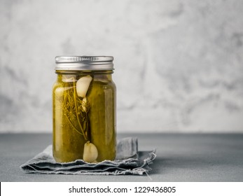 Glass jar with pickled cucumbers on gray background with copy space for text. Perfect homemade marinated cucumbers in mason jar on rustic table.