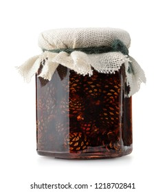 Glass jar of pine cone jam isolated on white