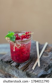 Glass jar of red currant soda drink on wooden table. Summer healthy detox lemonade, cocktail or another drink background. Low alcohol, nonalcoholic drinks, vegetarian or healthy diet concept.
