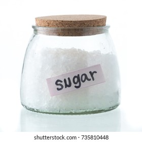 Glass jar with rock sugar isolated on white.