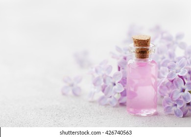Glass jar with rose water and lilac flowers for spa and aromatherapy, copy space for text.