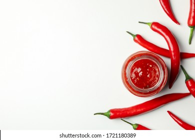 Glass jar with sauce and chilli pepper on white background, top view