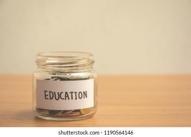 Glass jar saving money scholarship for education in future on wood table,vintage,minimal.