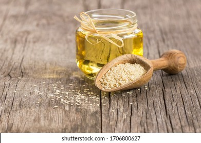 Glass jar of sesame oil and raw sesame seeds in wooden shovel with burlap sack on wooden table. Uncooked sesame background concept with copy space