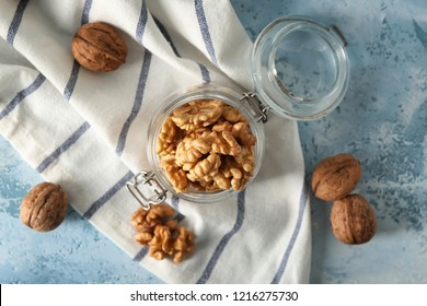 Glass jar with shelled walnuts on table