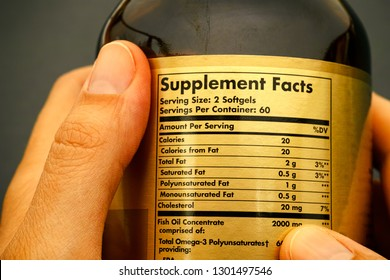 Glass jar with supplement facts in woman hands. Close-up.