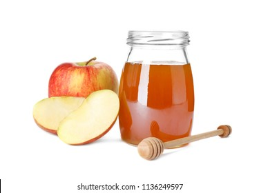 Glass jar with sweet honey and apples on white background