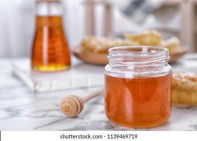Glass jar with sweet honey and dipper on table, closeup