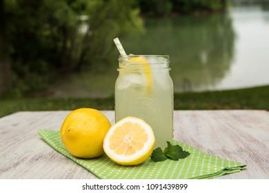 Glass jar of tasty lemonade with lemons on green napkin outside by the lake in summer