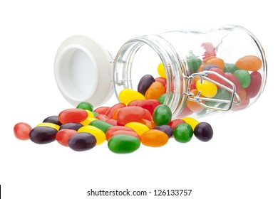 A glass jar tipped over, spilling its jelly beans