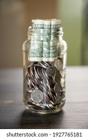 A glass jar with US coins and bills.