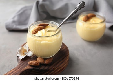 Glass jar with vanilla pudding with almond on table