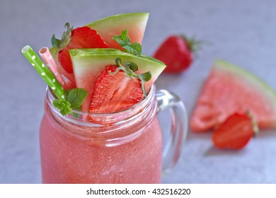 Glass jar with watermelon smoothie and strawberry