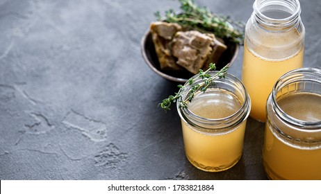 Glass jar with yellow fresh bone broth on dark gray background. Healthy low-calories food is rich in vitamins, collagen and anti-inflammatory amino acids