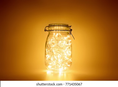 Glass jar with yellow light garland inside