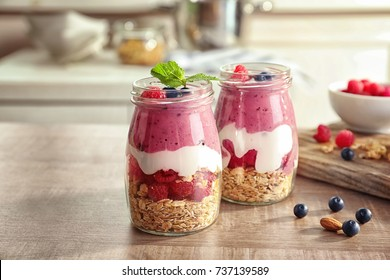 Glass jars with acai smoothie and berries on blurred background