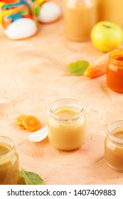 Glass jars of baby puree with spoons on pink background. Natural baby food concept.