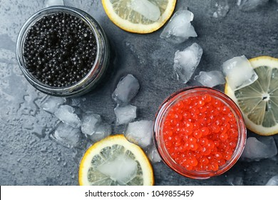 Glass jars with black and red caviar on grey background